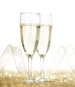Two champagne glasses and golden shiny glitters isolated on white background